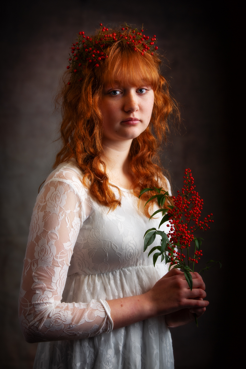 A red haired teenage girl wearing a white dress with red berries in her hair. Looking at the camera holding a small branch with more red berries and green leaves. The image is dark and moody but the red of her hair and the berries make the image pop.