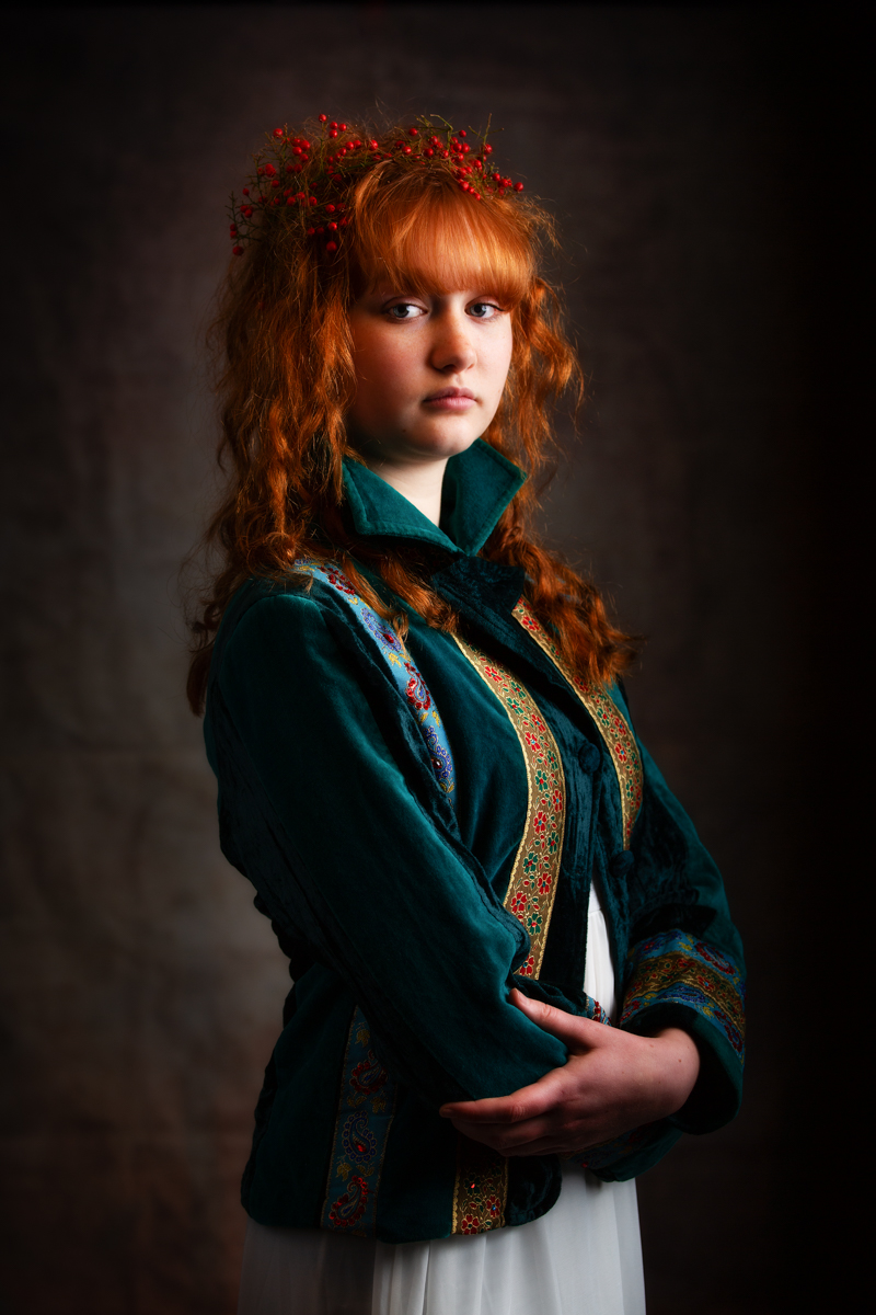 A teenage girl with long auburn hair has her arms gently folded and is looking seriously at the camera. She is wearing a dark green velvet jacket which has red and green patterned strips on it. In her hair she has red berries almost like a crown. Her expression is one of innocence and at the same time strength. Holding herself tall she appears to have a quiet confidence.