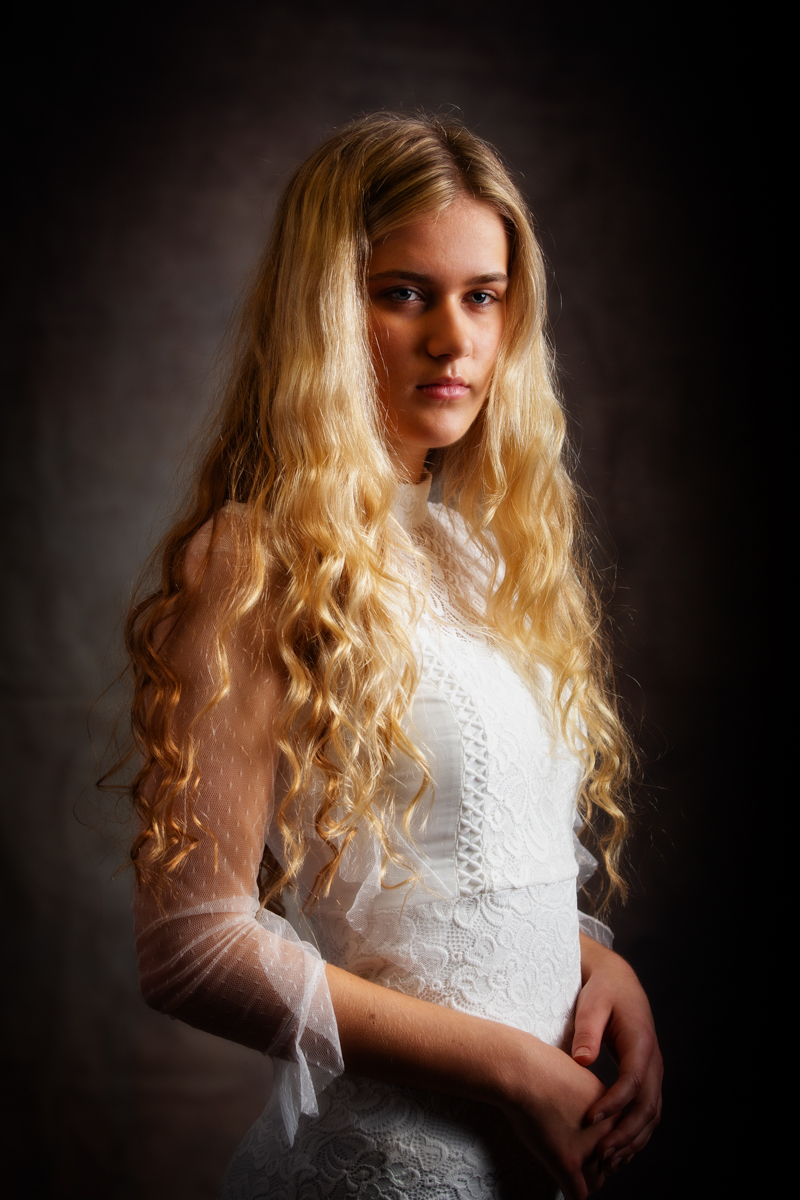 A young woman is looking off to the side, she is slim and wears a white lacy dress. Her hair is long down to her waist and is loose blonde hair.
