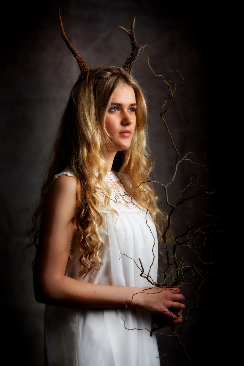A young woman dressed in white with bare arms holding a thin branch which is spiky and rambling. The woman has long blonde wavy hair which falls to her waist. On her head she has two small antlers, the background is dark and the colours are dark and light with the gold of her blonde hair and white dress in contrast to the darkness of the rest of the image.